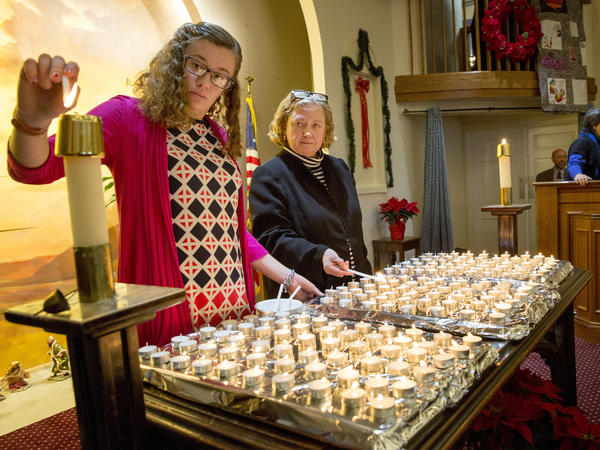 Elizabeth Hadley and Lisa Barbin light candles at the 28th annual Interfaith Homeless Memorial Service to remember homeless people who died in Boston in 2017.