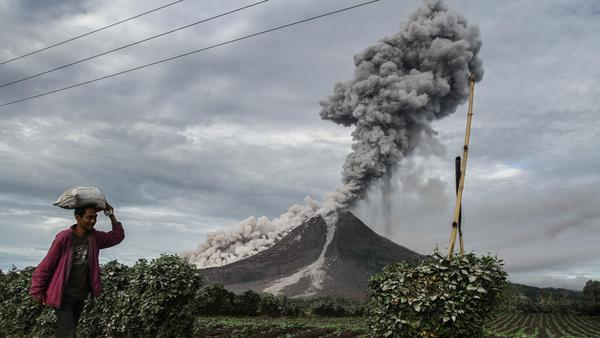 An Indonesian farmer passes a field as Mount Sinabung volcano spews thick smoke into the air in Karo, North Sumatra, earlier this month. The volcano roared back to life in 2010 for the first time in 400 years. After another period of inactivity it erupted once more in 2013, and it has remained highly active since.