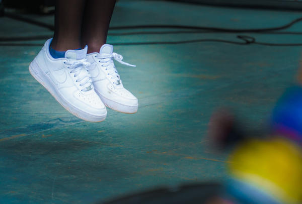 Clean, white Nikes worn by Jain, in the middle of a bouncing leap at the Container Bar in Austin, Texas during SXSW 2017.