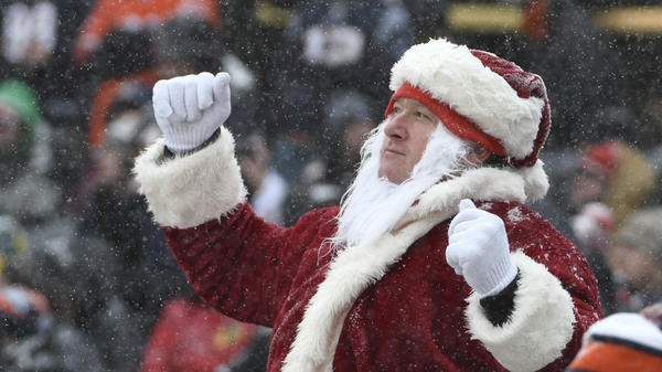 A fan dressed as Santa gestures in the snow during a game between the Chicago Bears and the Cleveland Browns in Chicago on Sunday. The storm system that brought Christmas Eve snow to Chicago is now passing over the Northeast.