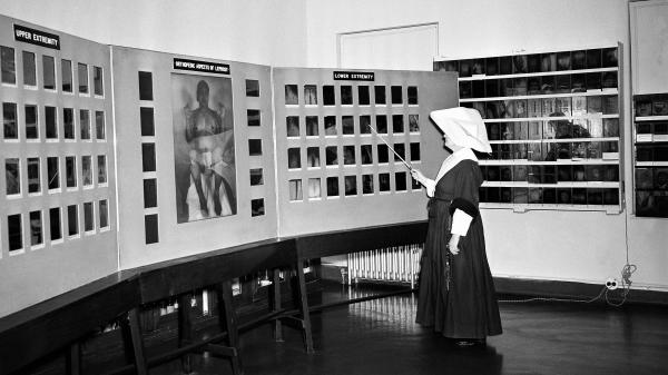 Sister Hilary Ross, a biochemist and clinical photographer at the Carville leprosarium, looks over an exhibition of color photos in 1952.