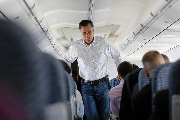 Mitt Romney talks to staff on his campaign plane en route from Reno to Elko, Nev., on Friday following a big win in the Florida primary.
