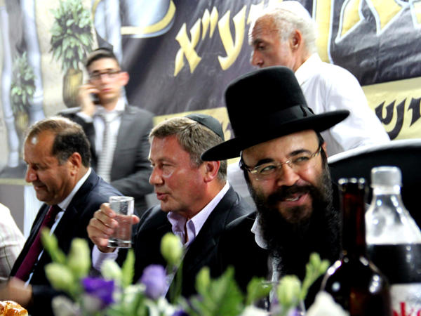 Ifargan, right, sits next to businessman Nochi Dankner, center, at an annual gala in Netivot, Israel, that honors the rabbi.