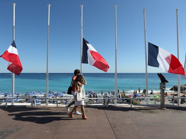 """French flags are seen lowered at half-staff in Nice on July 16. The truck attack on July 14 killed 84 people. """"I felt coming to celebrate on holiday and people are in mourning didn't seem right,"""" one vacationer says. """"But I'm glad I came."""""""