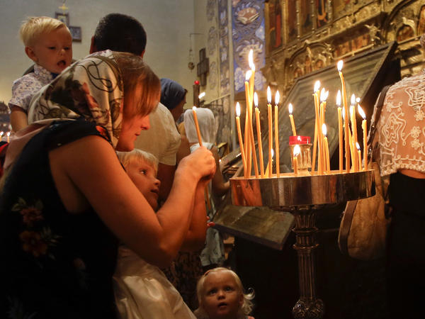 Three days after the Bastille Day attack, people light candles during a mass at Nice's Saint Nicolas Orthodox Cathedral.