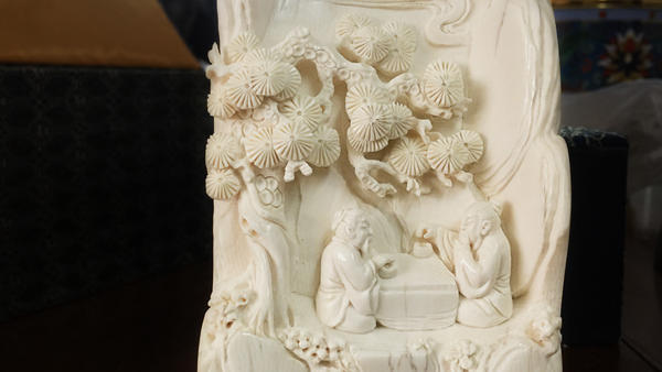 An ivory carving made from a piece of scrap by an apprentice of carver Li Chunke shows two men playing Go under a pine tree.