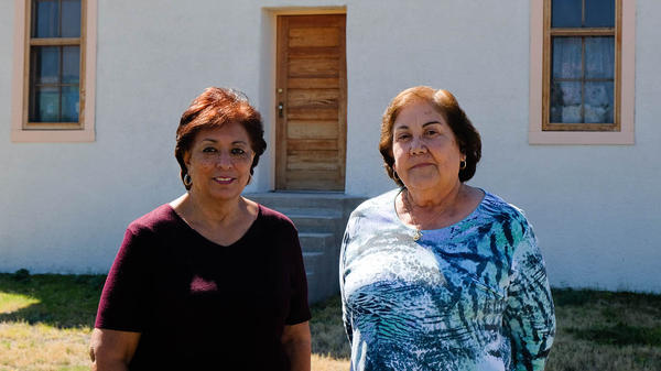 """Jessi Silva and Maggie Marquez on the grounds of the Blackwell School in Marfa, Texas. The school closed in 1965 and some of it was demolished. Both women returned to the grounds in 2007 with a group of alumni to hold a symbolic ceremony to unearth """"Mr. Spanish."""""""