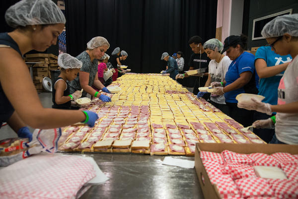 """Volunteers assemble tens of thousands of sandwiches each day at the Coliseo in San Juan, Puerto Rico. Chef José Andrés, who is overseeing the massive effort to feed displaced Puerto Ricans, calls it """"one of the most effective sandwich lines made by volunteers in history — I'm so proud of them."""""""