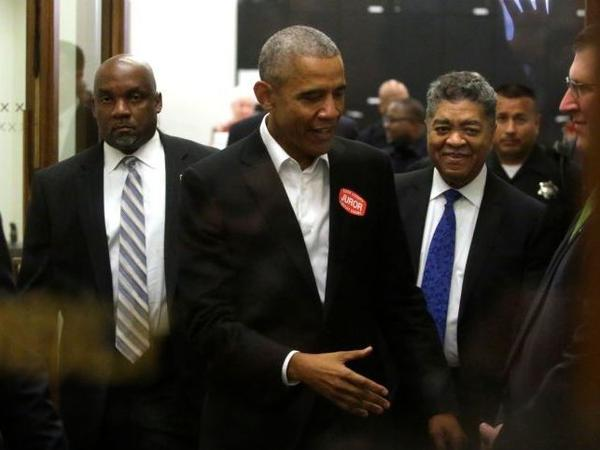 Former President Barack Obama extends his hand as he attends Cook County jury duty at the Daley Center on Wednesday in Chicago.