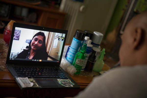 Dr. Gita Agarwal of Mary's Center conducts a telemedicine conference with Dennis Dolman from his mother's house in Washington, D.C.
