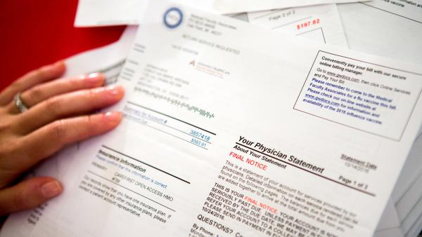 Christina Arenas reviews her medical bills at home in Washington, D.C. She complained about a mammogram and ultrasounds that she felt were unnecessary and sought a refund.
