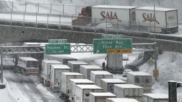 Early-morning traffic backs up on Interstate 5 during a Jan. 11 snowstorm in Portland, Ore. Truck drivers say such conditions, combined with limitations on their working hours, cost them a lot of money because of their mileage-based pay.
