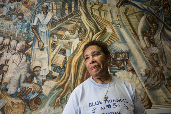 Charlotte Kelly Bryant, the Blue Triangle Multi-Cultural Association's founding president, stands in front of the John Biggers' 1953 mural, Contribution of Negro Women to American Life and Education, at the association's headquarters in Houston's Third Ward. The mural was damaged during Hurricane Harvey.