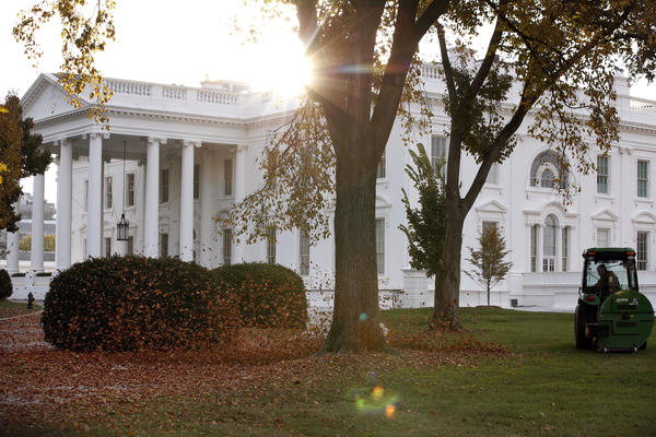 A tractor uses a leaf blower to gather the fallen leaves on the North Lawn as the sun rises over the White House on Nov. 18, 2017.