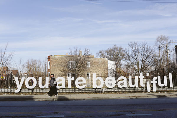 "People are seen walking past the ""You Are Beautiful"" sign, an art installation by Matthew Hoffman, in the Englewood neighborhood on Chicago's South Side. Nearly half of the people in this African-American neighborhood live below the poverty line, and many seniors have no idea there are public services that might help them."