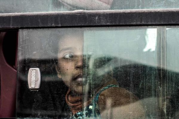 An Iraqi girl looks out the window of a bus transporting women and children to a camp for displaced people.