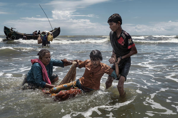 Rohingya refugees scramble off a fishing boat from Myanmar as it nears the beach at Dakhinpara, Bangladesh, on Sept. 14.