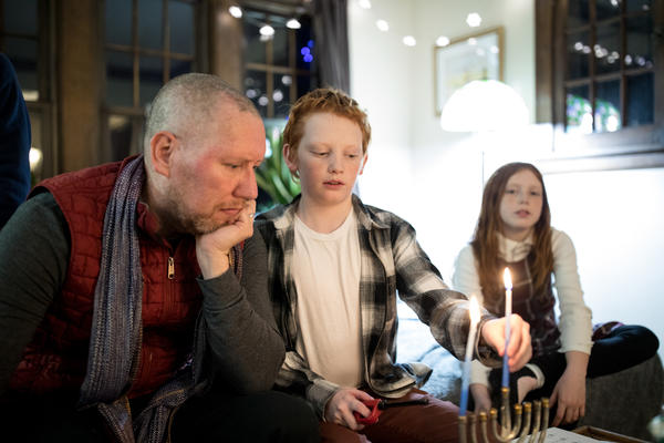 Carl Luepker, his son Liam, 12, and daughter Lucia, 11, light the menorah during Hanukkah in their home in Minneapolis, Minn. Carl and Liam both have a degenerative nerve disorder called dystonia.