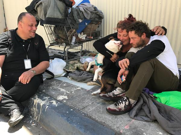 Eric Smith, left, talks to a homeless couple in San Francisco during neighborhood rounds. He's patient coordinator at the Haight-Ashbury Free Clinics, and wants to make sure they know they can get health care and addiction treatment there.