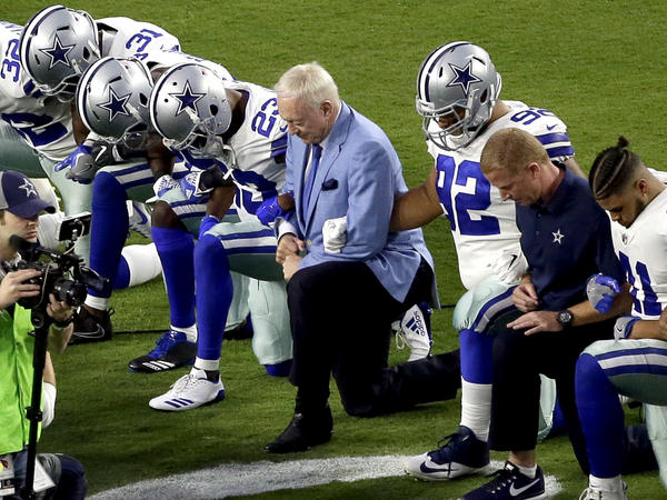 The Dallas Cowboys, led by owner Jerry Jones, center, take a knee prior to the national anthem before an NFL football game against the Arizona Cardinals in Glendale, Ariz., on Sept. 25.