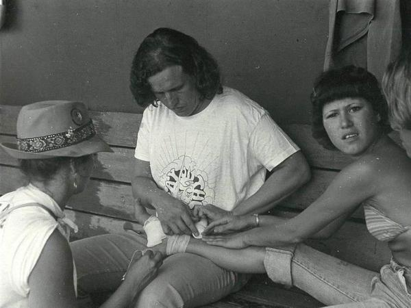 Dr. David Smith (second from left) helps a young woman by bandaging her feet as part of the clinic's street medicine in 1968.