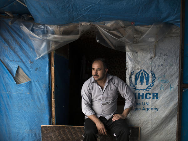 Suleiman Ibrahim Osman, from Syria, sits outside his tent in the Kawergosk refugee camp in northern Iraq in April. He's one of millions of people worldwide who have recently been forced out of their homes from war.