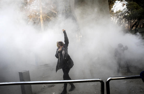 A university student takes part in a protest inside Tehran University while a smoke grenade is thrown by anti-riot Iranian police on Saturday. Iran has seen its largest anti-government protests since the disputed presidential election in 2009.