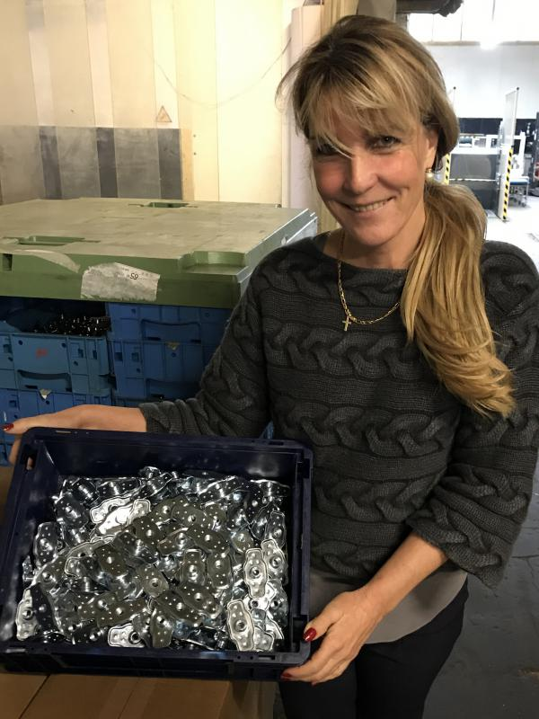 Yvonne Schmittenberg holds a tray of weld nuts produced by Schmittenberg Metal Works. They're used in the automotive industry.