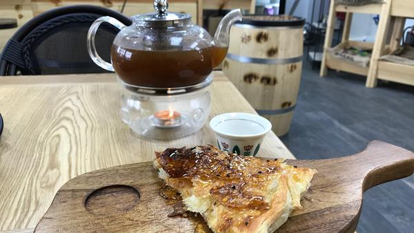 A traditional pot of Yemeni coffee, mixed with cardamom and ginger, is served with a Yemeni sweet honey bread at a new Yemeni coffee shop in Dearborn, Mich. Owner Ibrahim Alhasbani sees himself as part entrepreneur, part cultural ambassador for his home country.
