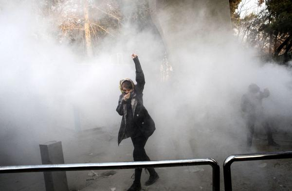 An Iranian woman raises her fist amid the smoke of tear gas at the University of Tehran during a protest  on December 30, 2017.