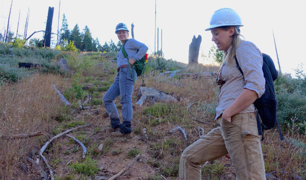 <p>Sydney Watkins (left) and Sara Galbraith hike up a steep slope was that severely burned in 2013.</p>