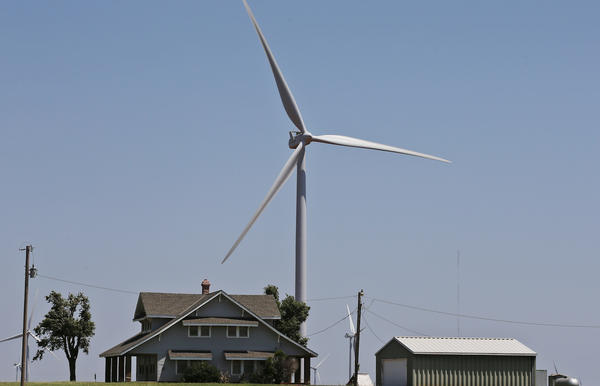 In this Monday, June 12, 2017 photo, a house is dwarfed by a near-by wind turbine near Okarche, Okla. (AP Photo/Sue Ogrocki)