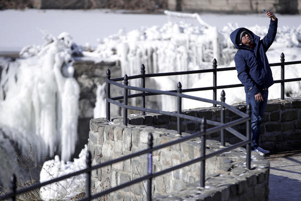 Obdulio Arenas takes a selfie at the partially frozen waterfall at the Paterson Great Falls National Historical Park, on Tuesday in Paterson, N.J.