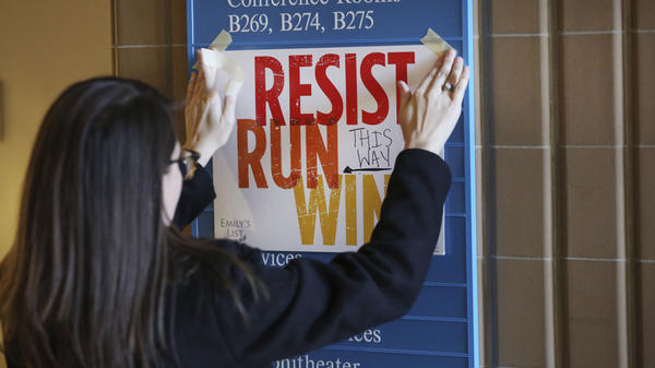 In this Saturday, Dec. 9, 2017 photo, Lianna Stroster posts a sign directing to a women's candidate training workshop at El Centro College in Dallas.