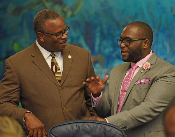 Rep. Shevrin Jones, right, speaks with Rep. Larry Lee on the floor of the state House of Representatives last year. Jones, a Broward County Democrat, has proposed a new college scholarship for low-income students.
