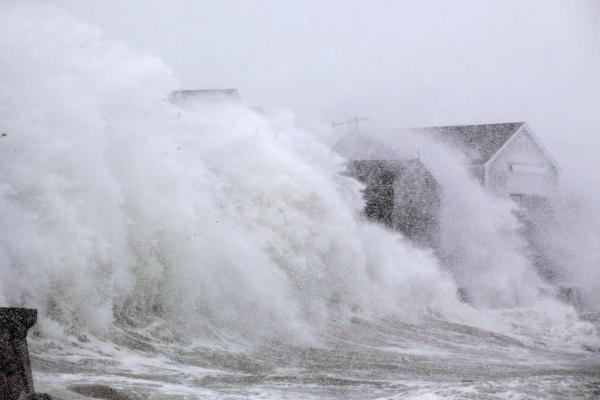 "A wave crashes over homes in Scituate, Mass., as a massive winter storm begins to bear down on the region. The ""bomb cyclone"" is expected to dump heavy snows in New England as the storm system moves up the East Coast."