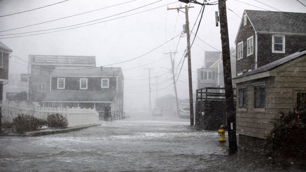 A road begins to flood in Scituate, Mass., during a massive winter storm on Thursday.