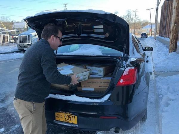 New Paltz Town Supervisor Neil Bettez loads tax bills into an old police car to take to residents at the town hall last week.