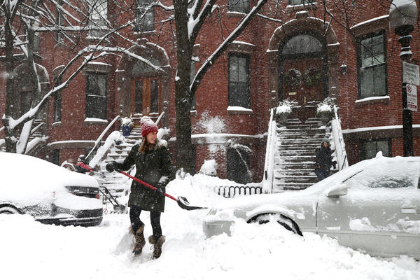 A woman clears the steps in front of her home in Boston.