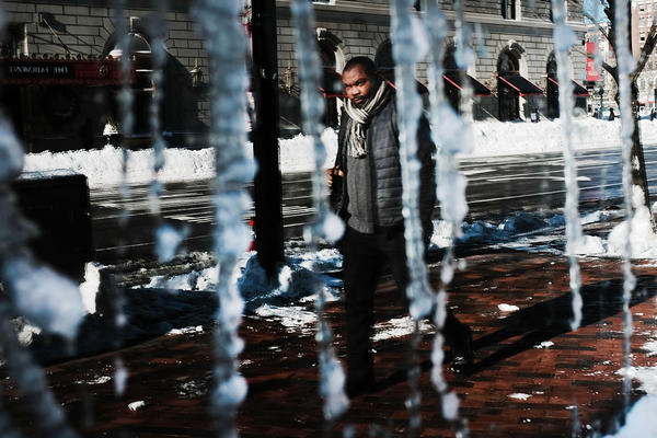A man is reflected in a frozen window in Boston. The National Weather Service said early Friday that very cold temperatures and wind chills will follow for much of the Northeast through the weekend.