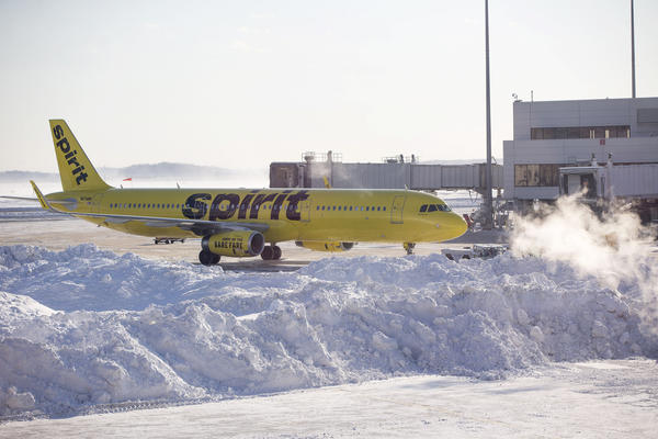 A Spirit Airlines airplane prepares to drive around a large snow pile at Logan International Airport in Boston. Hundreds of flights were cancelled and delayed because of the storm.