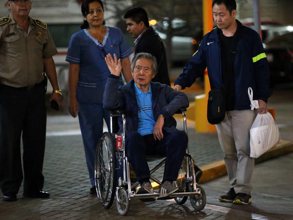Former President Alberto Fujimori waves to supporters Thursday as he is wheeled out of a hospital, where he received his Christmas Eve pardon from President Pedro Pablo Kuczynski.