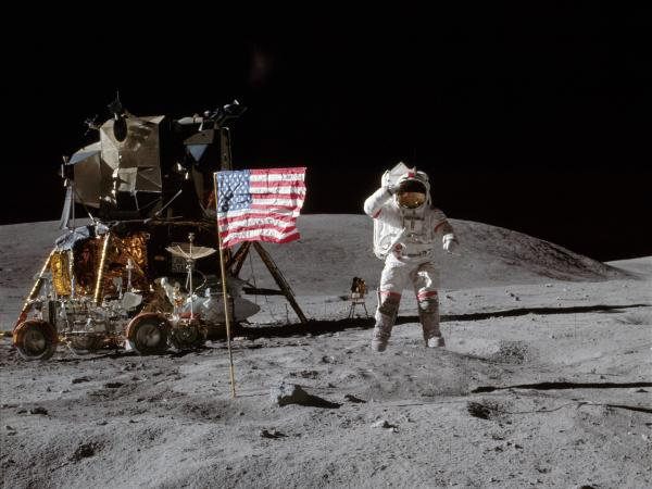 On the moon in 1972, Apollo 16 astronaut John Young jumps off of the lunar surface to salute the U.S. flag.