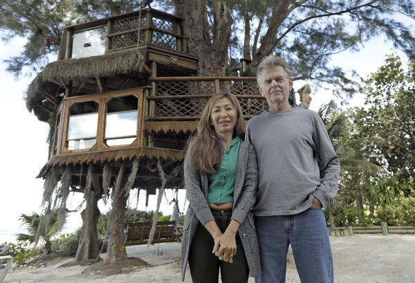 Lynn Tran and her husband Richard Hazen pose near their Australian pine treehouse Thursday, Jan. 4, 2018, in Holmes Beach, Fla. The couple is hoping the U.S. Supreme Court will hear their case after city and state officials ordered the treehouse removed.