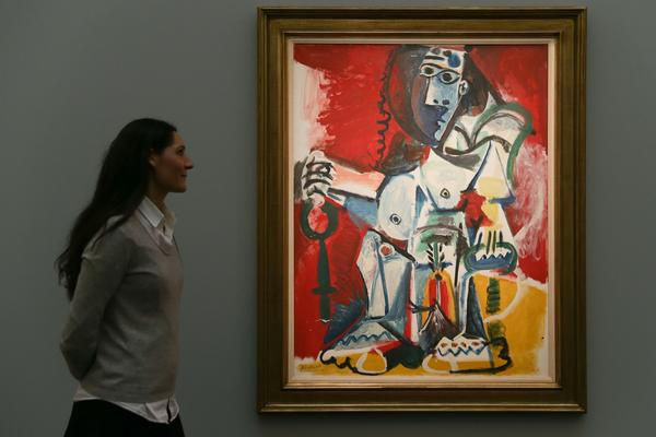 "An employee poses with an artwork by Spanish artist Pablo Picasso, entitled ""Femme new assise, 1965"", with an estimated price of 9.5-12.5 million GBP (11-15 million EUR; 12-15.5 million USD), during a photocall ahead of the Impressionist & Modern, Surrealist and Contemporary Art sale at Sotheby's in London, on February 22, 2017."