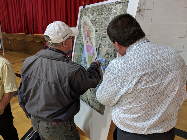 KDHE employee Kevin Moon, right, helps a Haysville resident locate his house on a map during a December 5, 2017, public meeting.