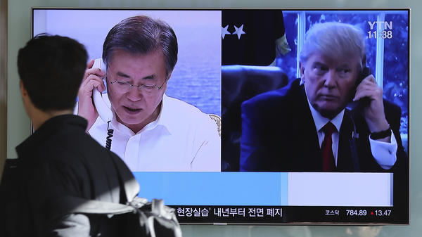 """In December at the Seoul Railway Station in South Korea, a man walks by a TV report about North Korea's missile launch with images of U.S. President Trump and South Korean President Moon Jae-in. On Wednesday, Trump and Moon spoke by phone and Trump expressed openness to U.S.-North Korea talks """"at the appropriate time, under the right circumstances."""""""