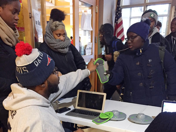 Ezzard Turner, a dean at the City on a Hill Circuit Street charter school in Boston, returns students' phones after locking them in pouches for the school day. A new policy at the school aims to literally contain distractions by requiring the phones to stay locked up until dismissal time.