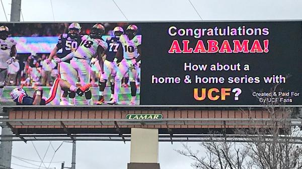 Perched on McFarland Boulevard in Tuscaloosa, home of the Alabama Crimson Tide, a new billboard bought by UCF fans lays down the gauntlet — which, it must be noted, is all but assured of not being picked up.