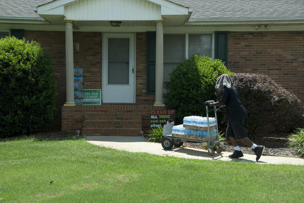 A worker delivers bottled water to a home in Belmont, near Duke Energy's Allen coal plant. Duke will provide a permament drinking water supply to well owners by Oct. 15, 2018.